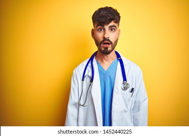 Young doctor man with tattoo wearing stethocope standing over isolated yellow background afraid and shocked with surprise expression, fear and excited face.