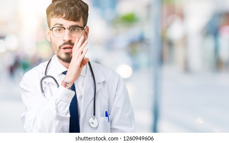 Young doctor man wearing hospital coat over isolated background hand on mouth telling secret rumor, whispering malicious talk conversation