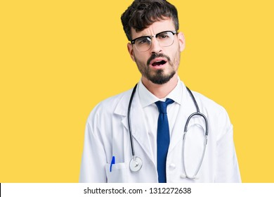 Young doctor man wearing hospital coat over isolated background In shock face, looking skeptical and sarcastic, surprised with open mouth