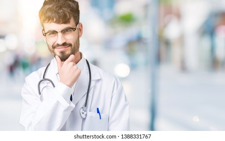 Young doctor man wearing hospital coat over isolated background looking confident at the camera with smile with crossed arms and hand raised on chin. Thinking positive.