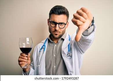 Young doctor man wearing stethoscope drinking a glass of fresh wine over isolated background with angry face, negative sign showing dislike with thumbs down, rejection concept