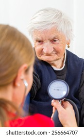 Young doctor measures the elderly woman blood pressure