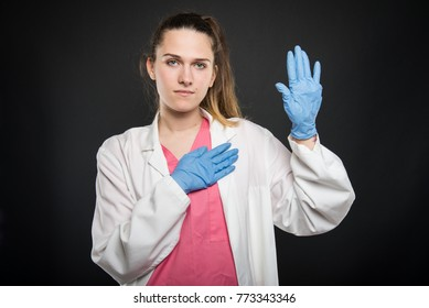 Young doctor portrait wearing robe taking Hippocratic oath on black background