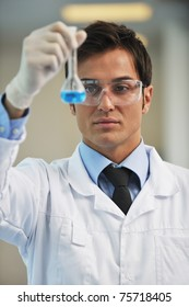 young doctor scientist in bright labaratory work research and  analyse content of  test tubes representing chemistry and research concept