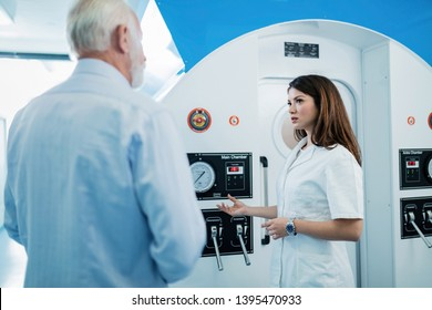 Young doctor and senior man standing in front of hyperbaric chamber and talking about oxygen therapy.