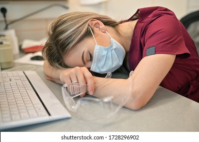 Young Doctor Sleeping On The Desk In Medical Office
