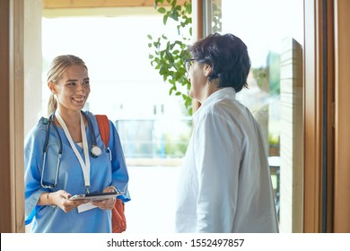 A young doctor is standing at the entrance to the house of a young woman and her little daughter