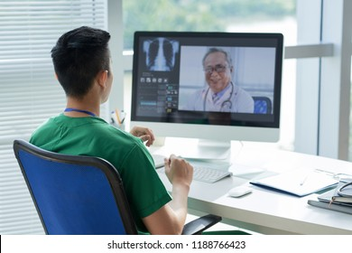 Young doctor talking to his experienced colleague via video conference