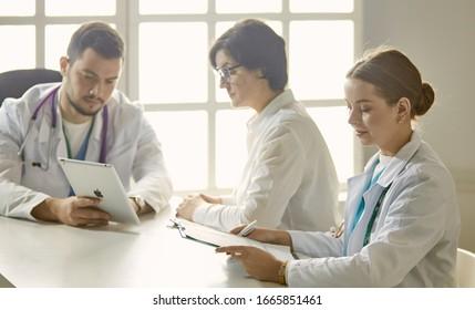 Junge Ärztin, die mit einem Patienten im Büro spricht