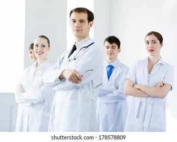Young doctor in uniform and colleagues at background