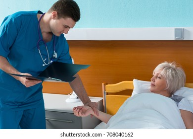 Young doctor in uniform with phonendoscope on his neck is measuring the pulse of his female patient, who is lying in the hospital bed in the hospital ward. Healthcare concept