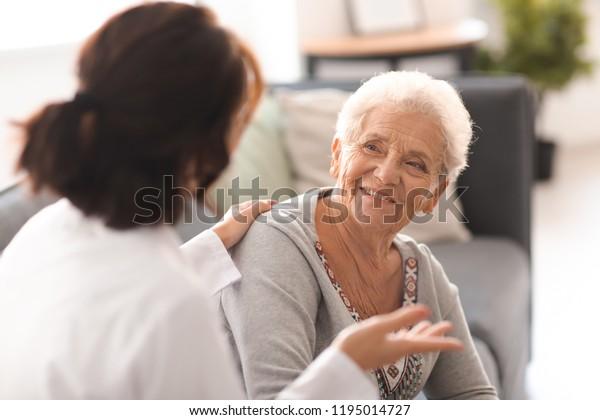 Junge Ärztin besucht ältere Frau zu Hause
