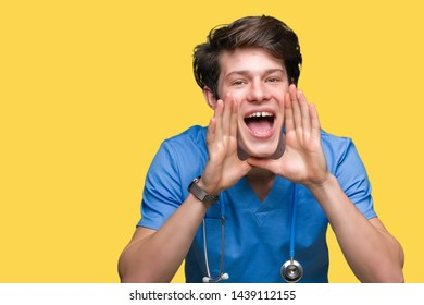 Young doctor wearing medical uniform over isolated background Shouting angry out loud with hands over mouth