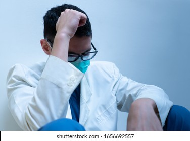 A young doctor in white gown feeling stressed, sitting in the room in the hospital. medical, healthcare, burnout, depression, covid-19, coronavirus concept