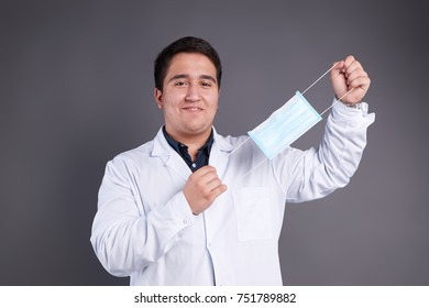 Young doctor in white lab coat and blue polo in medical mask