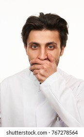 Young doctor in white uniform, hand covering mouth, shocked, isolated on white background. Close-up portrait