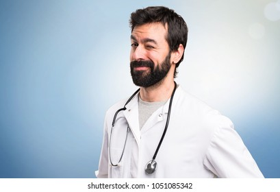 Young doctor winking on blue background