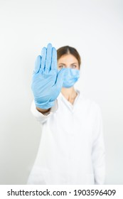 Young doctor woman, medical professional annoyed with bad attitude making stop sign with hand, saying no, expressing security, defense or restriction, maybe pushing