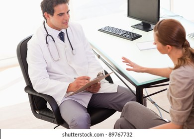 Young doctor writing down the symptoms his patient is describing