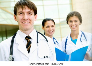 Young doctors are standing outside the hospital and looking at camera