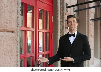 Young doorman in elegant suit standing near restaurant entrance