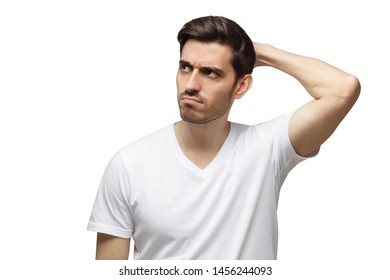 Young doubtful man scratching his head trying to find solution, isolated on gray background