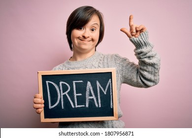 Young down syndrome woman holding blackboard with dream word as message of happiness surprised with an idea or question pointing finger with happy face, number one