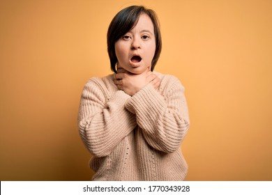 Young down syndrome woman wearing casual sweater over yellow background shouting and suffocate because painful strangle. Health problem. Asphyxiate and suicide concept.