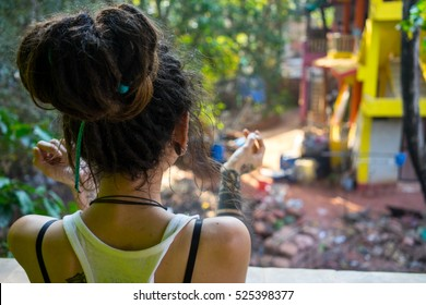 Young dread-headed girl smoking on the balcony of indian cottage and looking at the yard