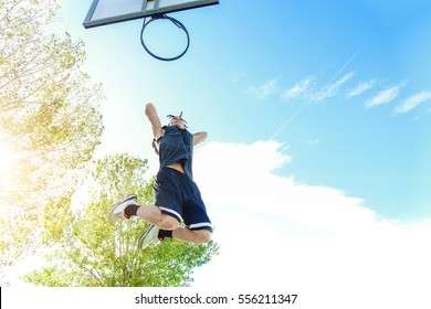 Young dreadlocks player dunking in urban city basketball court with back sun light - Strong athlete performing slam dunk at university  - Sport and school concept - Focus on his face - Warm filter