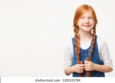A young dreamer thoughtfully looking in the upper left corner, imagines a delicious cake, standing next to an empty copy space isolated on a white. Nice child girl with two plaits of red-hair