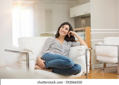 Young dreaming woman sitting on sofa at home. Thoughtful young woman sitting in living room and looking up. Smiling woman relaxing on couch in a modern home.