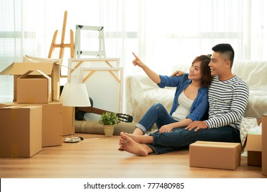 Young dreamy Asian couple sitting on the floor after moving in new apartment