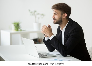 Young dreamy businessman in suit thinking of business vision outlook planning future project idea at work with laptop, successful happy contemplative entrepreneur dreaming of new opportunity prospect