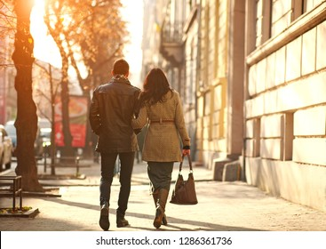 Young dreamy couple carefree walking along the streets of the old city at sunset, back view