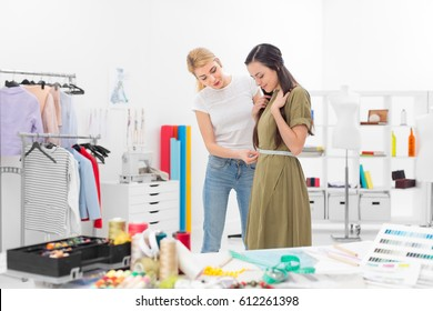young dressmaker gets waist measures of client in the showroom