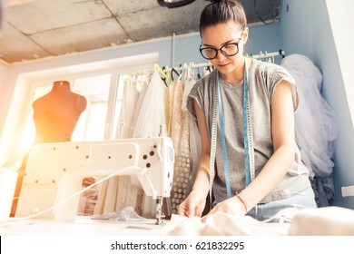 Young dressmaker woman sews clothes on sewing machine. Smiling seamstress and her hand close up in workshop. Focus on sewing machine and tissue.