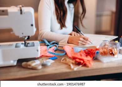 Young dressmaker woman is writing down ideas close-up. Creating online clothing design courses.