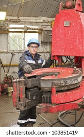 The young driller a wearing spectacles and protective suit drills well