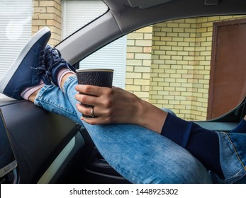 Young drinking coffee take away with feet in boots on car dashboard - Travel ,road trip