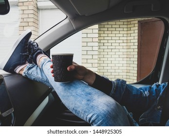 Young drinking coffee take away with feet in boots on car dashboard - Travel ,road trip with matte filter