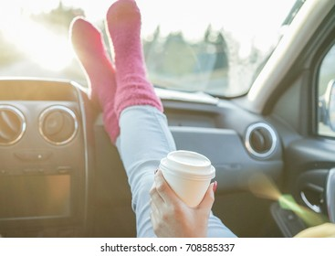 Young drinking coffee take away with feet in warm socks on car dashboard -  Travel ,road trip and winter concept - Focus on paper cup hand - Warm filter with original back sun light