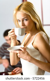 Young drinking woman with cup and cooking man at kitchen. Focus on woman.