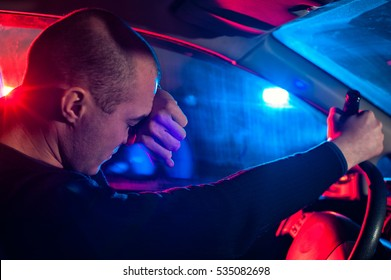 Young driver with alcohol bottle covering his face from police car light. He was caught driving under alcohol influence