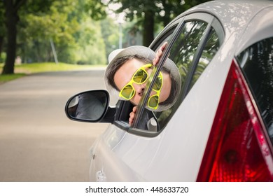 Young driver with hat and sunglasses sticks out from car window. Travel, on the road and vacation concepts.