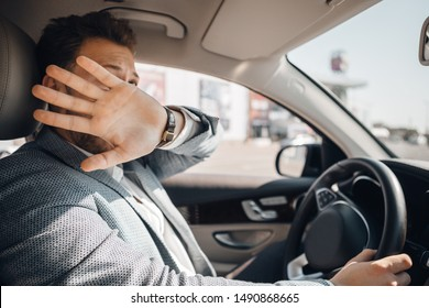 Young driver hides his face and looks scared because of dangerous traffic situation that could cause sad accident. Concept of car safety.