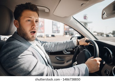 Young driver looks scared because of dangerous traffic situation that could cause sar accident. Concept of car safety.