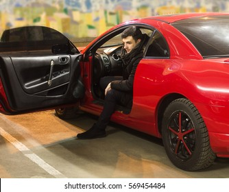 young driver sitting in sport car with opened door