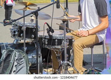 Young drummer playing drum kit in street. Closeup