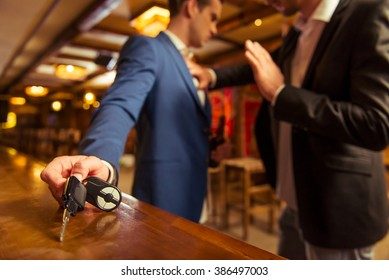 Young drunk businessman is holding a bottle of beer and reaching car keys on bar counter in pub, another man is stopping him
